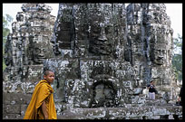 A monk walks in front of one of the Bayon's many faces. Siem Riep, Angkor, Cambodia