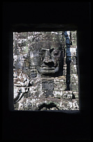 One of the smiling faces in the Bayons seen through a window. Siem Riep, Angkor, Cambodia