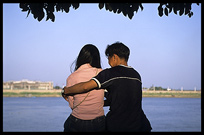 A young Cambodia couple is enjoying the view of the Mekong at Phnom Penh's riverfront.