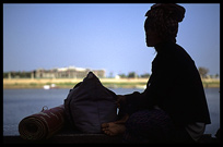 Silhouette of a Cambodian woman at Phnom Penh's riverfront.