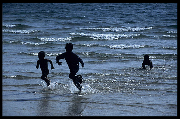 Silhouettes of Cambodian children at Sihanoukville.