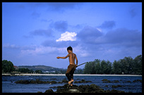 A Cambodian kid is fishing at a fishing community near Sihanoukville.