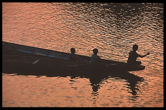 Boats returning home at sunset on the four thousand islands. Si Phan Don, Don Det, Laos