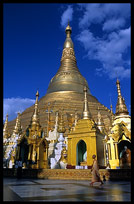 A buddhist nun walking in front of the great golden dome of Shwedagon Paya in Yangon.