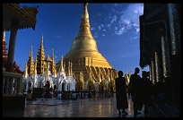 The silhouettes of monks in front of the great golden dome of Shwedagon Paya in Yangon.
