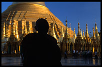 The silhouette of a monk in front of the great golden dome of Shwedagon Paya in Yangon.