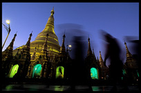 Magical moments at Shwedagon Paya. Silhouettes of devotees at night in front of the golden dome.