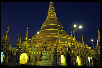 Buddhist nuns standing in front of Shwedagon Paya at night.
