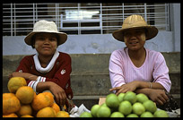 Two Burmese women selling apples and oranges at the Zeigyo (Central Market).