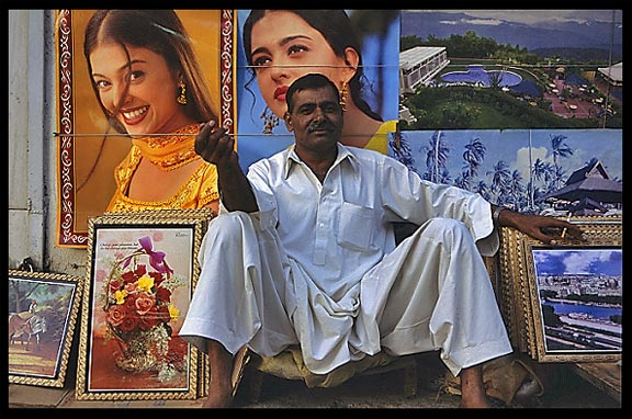 A merchant is selling posters of famous Indian movie stars. Lahore, Pakistan