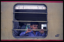 A boy looking out of the window at the train station. Taxila, Pakistan