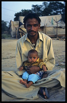 An Afghan refugee with his young child. Taxila, Pakistan
