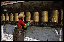 A Tibetan pilgrim walking the Potala Kora spinning prayer wheels. Lhasa, Tibet, China