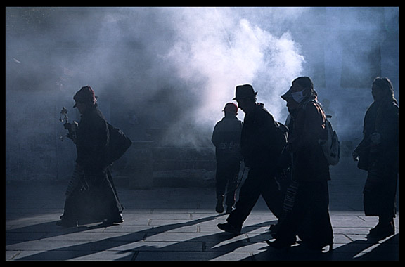 Smoke from the incense burners creates silhouettes of passing by pilgrims.