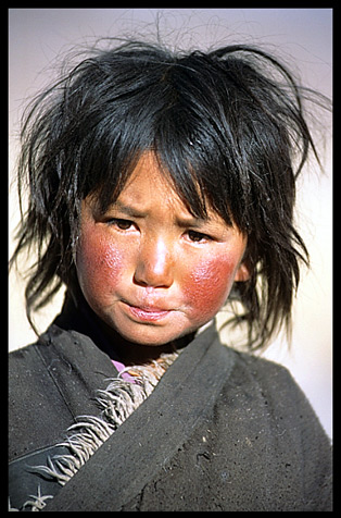 A Tibetan child with red cheeks from the cold, the height and the sun.