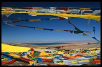 Tibetan prayer flags on the last mountain pass before Nam Tso. Lake Nam Tso appears in the background. Nam Tso, Tibet, China