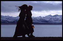 The silhouettes of two Tibetan pilgrims with the snowy Nyenchen Tanglha massif (7111m) in the background. Nam Tso, Tibet, China