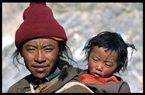 A Tibetan pilgrim and his young child are walking the Kora at Nam Tso. Nam Tso, Tibet, China