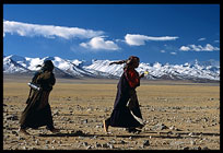 Tibetan pilgrims walking the Nam Tso Kora with the Nyenchen Tanglha massif (7111m) in the background. Nam Tso, Tibet, China