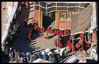 Tibetans travel hundreds of kilometers to bring their deceased relatives to Drigung Til monastery for a sky-burial. Monks receive gifts in the main courtyard just before the sky-burial begins. Tibet, China